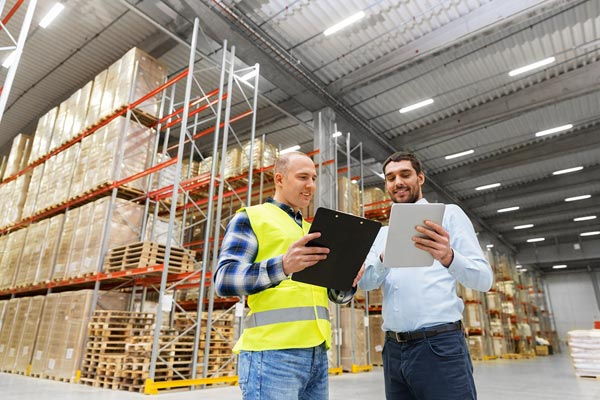Two logistics workers comparing freight plans in shipping warehouse