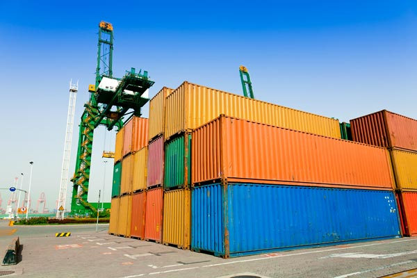 Different colored supply shipping containers near lift