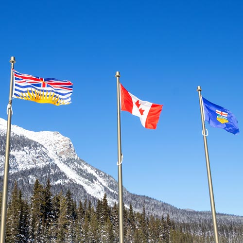 British of Columbia flag, Canadian Flag, and Alberta flag in front of snow topped mountains