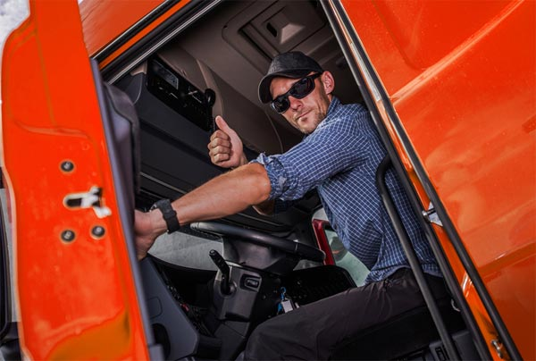 Truck driver giving thumbs up in his red semi truck