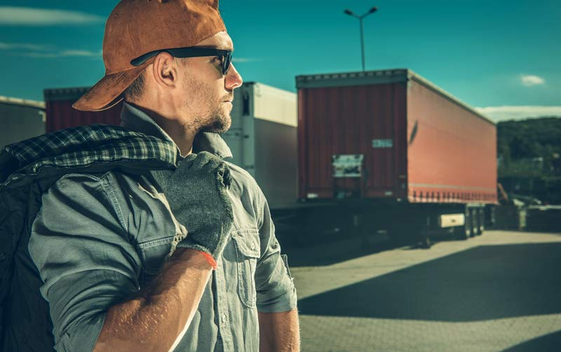 Man wearing backwards hat and sunglasses in front of logistics shipping containers