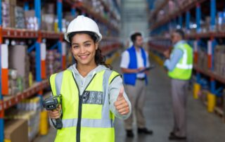 Woman wearing hard hat and safety vest giving a thumbs up in a logistics warehouse
